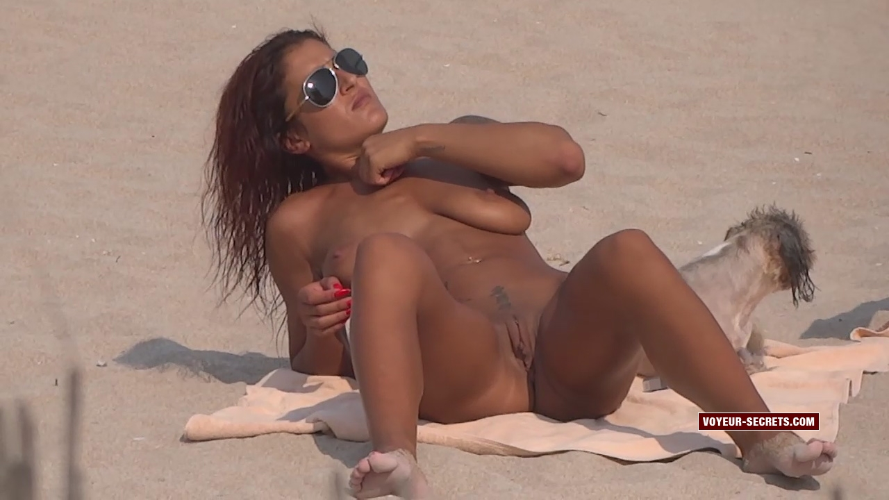 Hot tanned nudist woman sunbathes with spread legs beside her wet dog