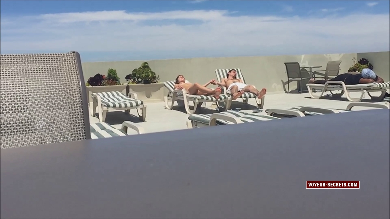 Naked girl relaxes with her older boyfriend at the hotel swimming pool