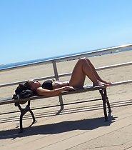 Amazing girl sunbathes on a bench
