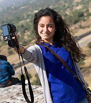 Adorable tourist girl makes selfies