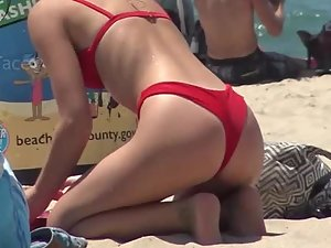 Teen in red bikini gets on all fours at the beach