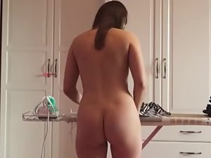 Naked wife ironing clothes at home