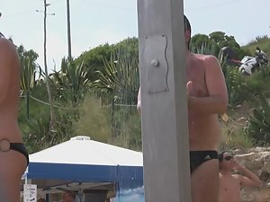 Naked woman with tattoos at beach shower Picture 1