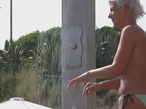 Naked woman with tattoos at beach shower Picture 3