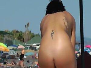 Naked tattooed girl on a beach