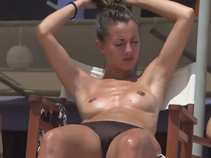 Oiled up beauty relaxes in topless