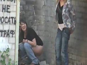 Women caught peeing behind an old wall
