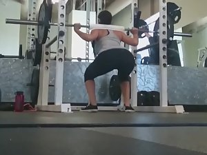 Fit girl squats in the gym