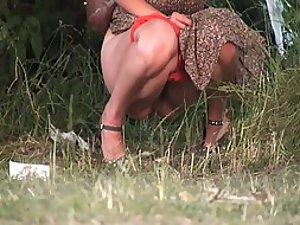 Milf removes red panties to piss in the park
