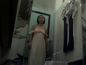 Spying on cute asian girl trying on dresses