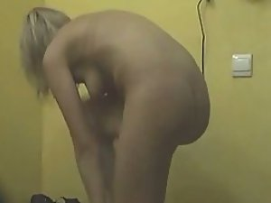 Naked blonde creams up before tanning