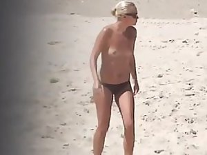 Topless beach babe in a thong bikini
