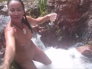 Naked woman enjoys herself in a waterfall