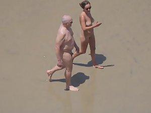 Zooming on weird nudist couple on beach