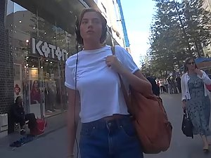 Smug busty girl walks and smokes a cigarette