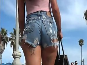 Tattooed girl in torn jeans shorts