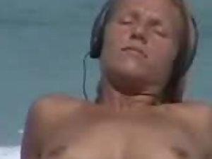 Blonde nudist girl listens to music