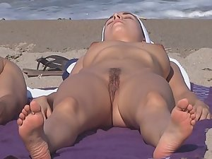 Undressing to full nudity on the beach