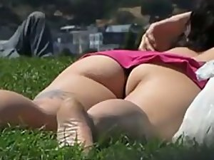Tattooed girl spied lying on the grass