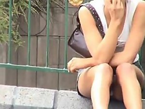 Upskirt of a girl sitting on a road curb