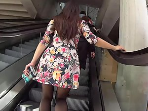 Upskirt of flowery dress on moving stairs