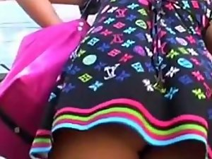Peeping under a happy girl's colorful skirt