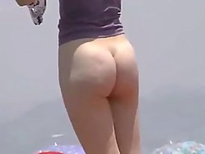 Sexy girl undresses at the beach