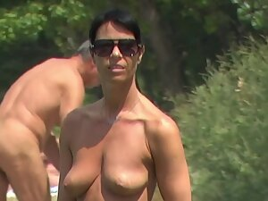 Topless milf with a much younger boyfriend at the beach